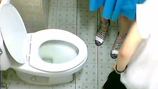 Two pretty Asian friends are pissing on toilet in café