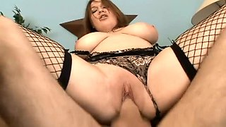 Chubster with huge tits in fishnets rides big dick with pleasure