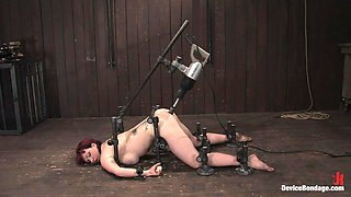 Busty redhead fucked by fuck machine in bondage scene