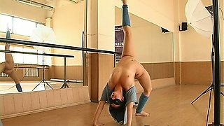 Flexible gymnast girl posing naked in the gym
