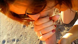 Horny wife rubs her pussy and strokes a cock on the beach