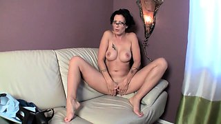 Slender brunette milf with glasses masturbates on the couch