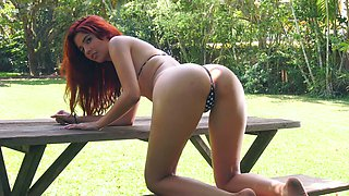 Curly red haired babe Agatha Vega is pleasing herself in the garden