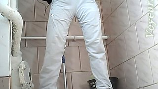 Beautiful tall brunette chick in white jeans pisses in the toilet