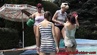 Lesbian foursome by the swimming pool