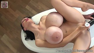 Passionate brunette with gigantic milk jugs is toying her wet pussy with a big, black dildo