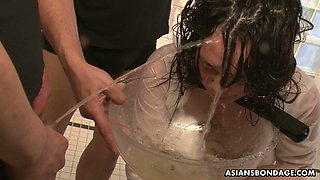 Crazy dudes fuck Asian hooker in the cage and piss on her face and tits