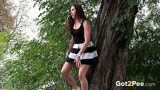Hot brunette in splendid dress urinates in the woods