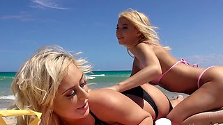 Two babes are at the beach, rubbing lotion on each other well